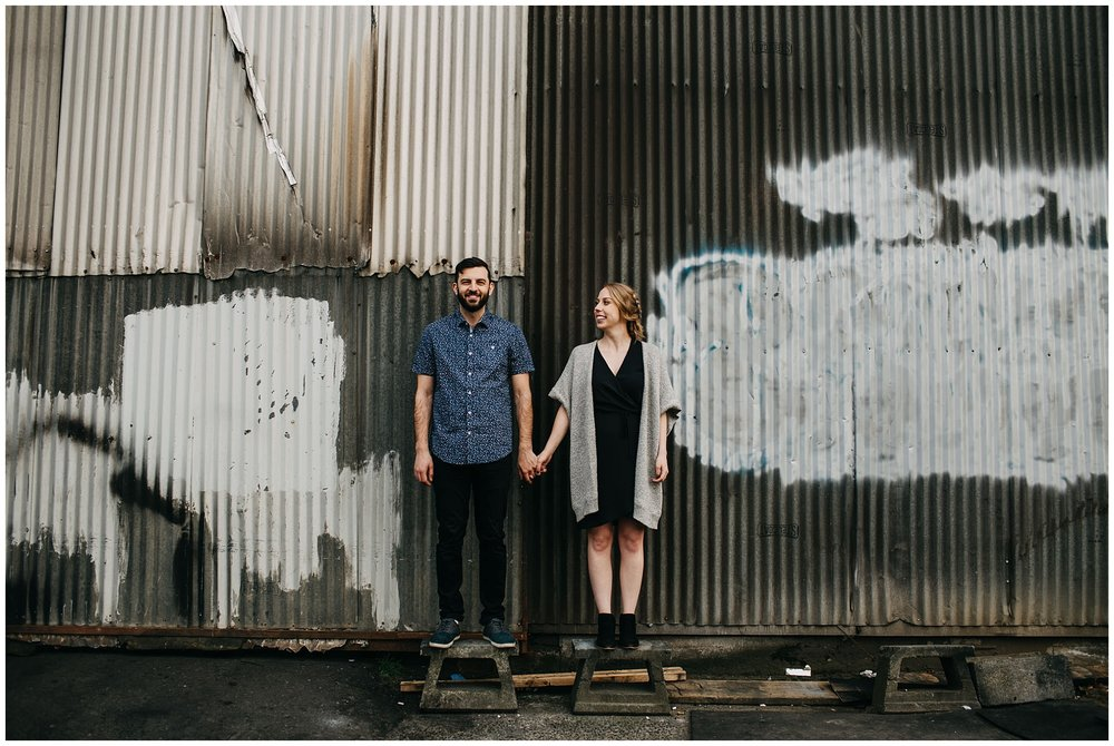 couple holding hands in industrial urban setting at downtown new west engagement session