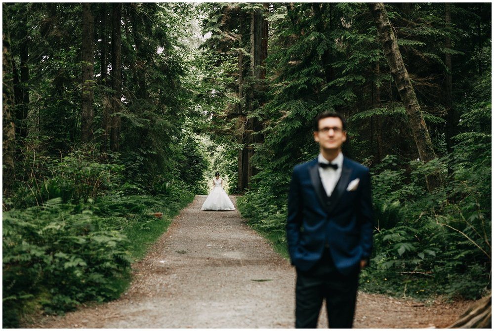 bride walking towards groom in forest for first look at stanley park wedding