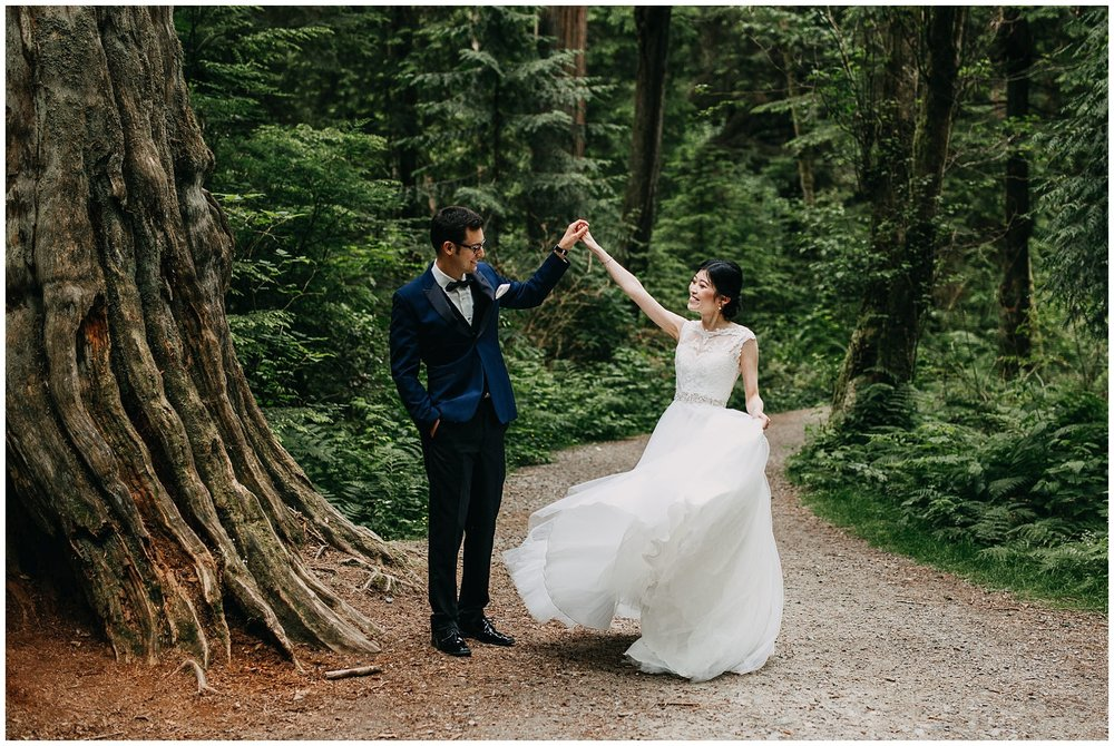groom twirling bride in the forest at stanley park wedding