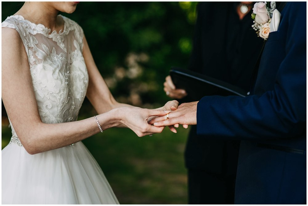 bride and groom exchanging rings at stanley park teahouse wedding