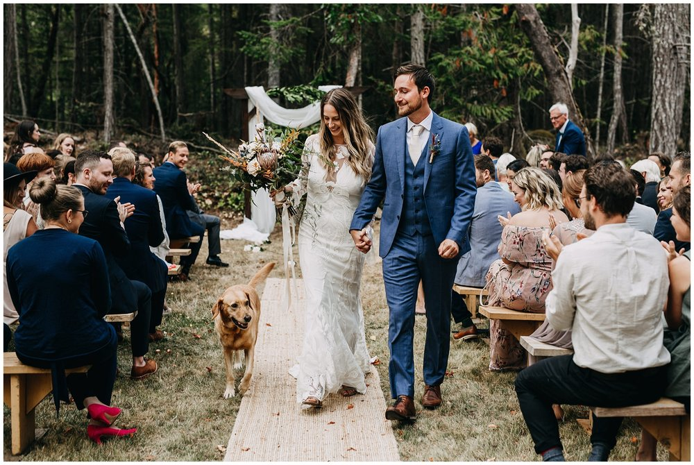 bride and groom ceremony exit with dog at intimate mayne island backyard wedding