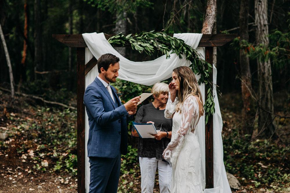 bride and groom exchanging vows at intimate mayne island backyard wedding