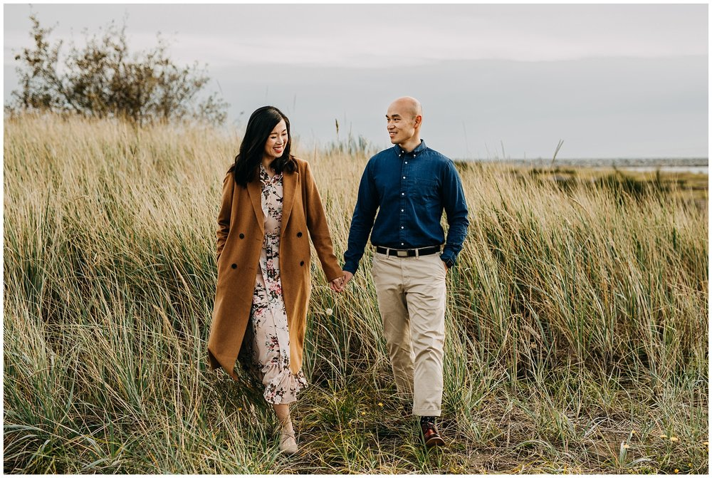 couple walking in tall grass at iona beach engagement session