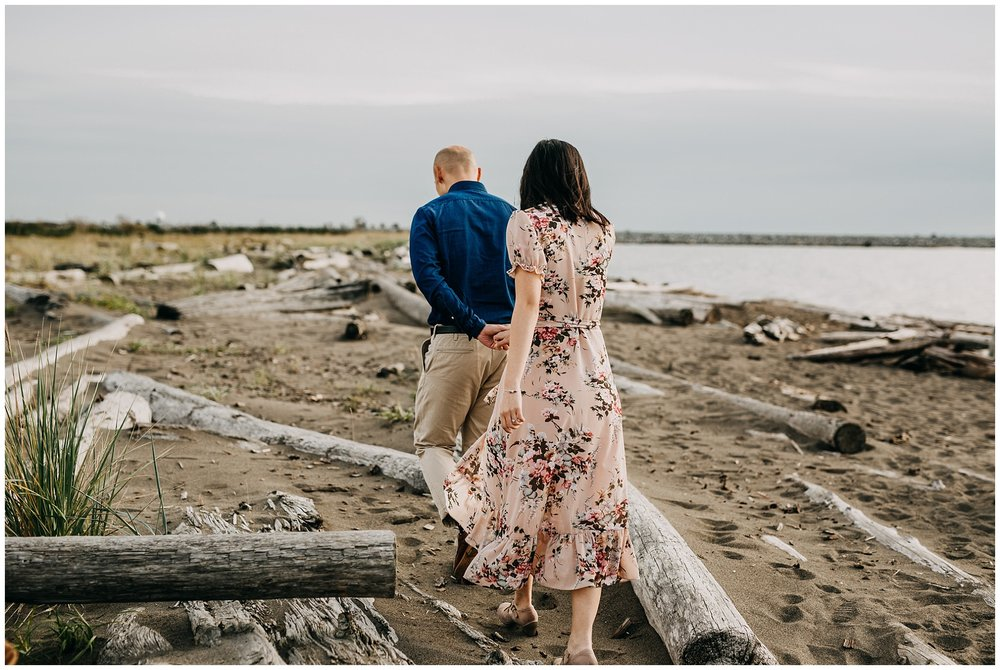 couple walking on beach at iona beach vancouver engagement