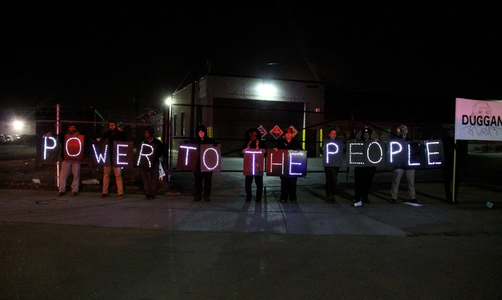 "Detroit Light Brigade with ""Power to the People"" signs outside the State of the City address. Photo Credit: Shanna Merola"