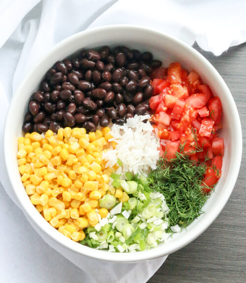 a plate full of bean rice and corn salad