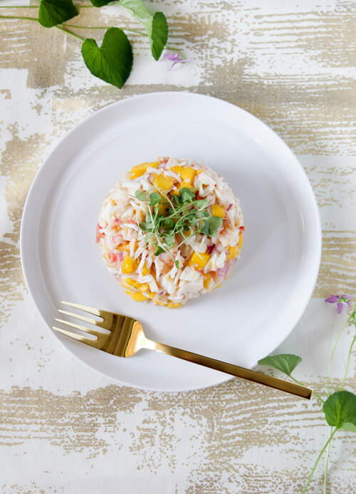 A plate full of mango and crab salad