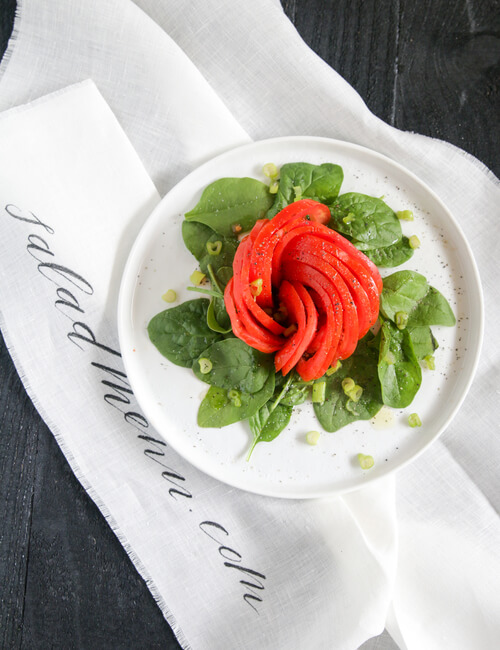 A plate of tomato and spinach salad