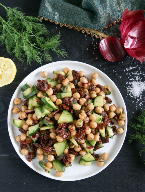 A plate of chickpea salad with cucumber and sun-dried tomato