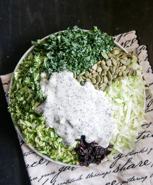 A bowl of superfood kale salad with poppy seed dressing