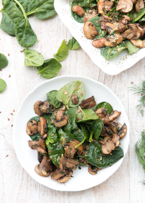 A plate of mushroom salad with spinach and flax seeds