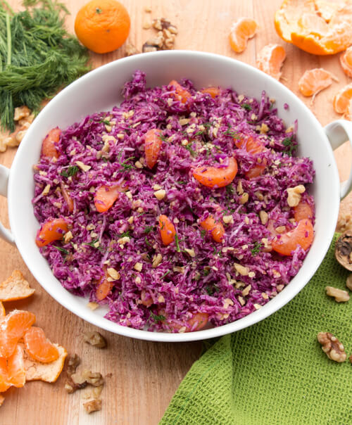 A plate of purple cabbage with mandarins and walnuts