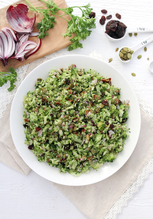 A plate of broccoli salad with pumkin seeds and bacon