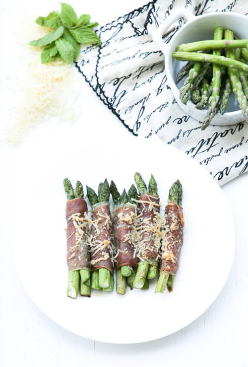 A plate of prosciutto wrapped asparagus and cheese