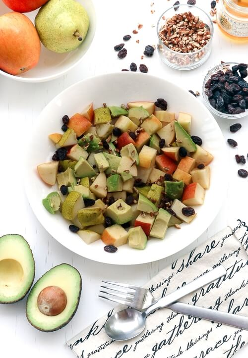 A warm bowl of fruit pecan avocado raisin salad with sweet dressing