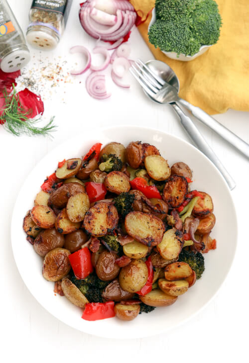 A plate of seasoned roasted potatoes with vegetables
