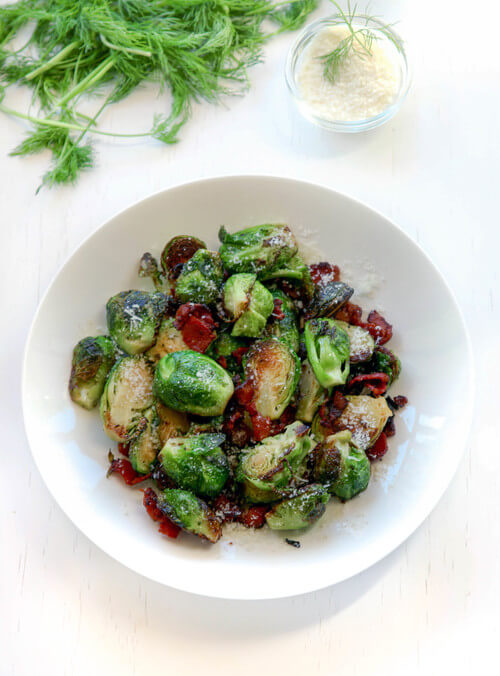 A plate of seared brussel sprouts with bacon and cheese
