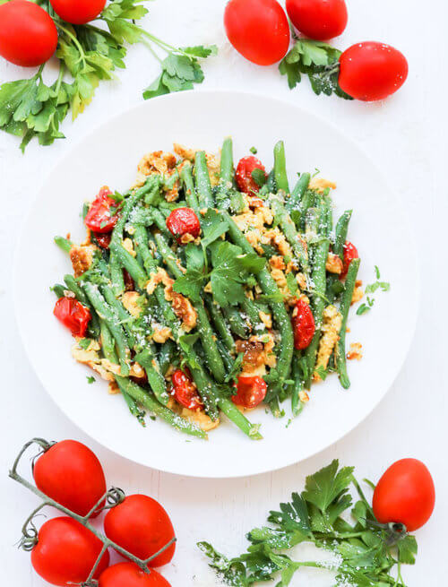 A plate of green beans with eggs tomato and cheese