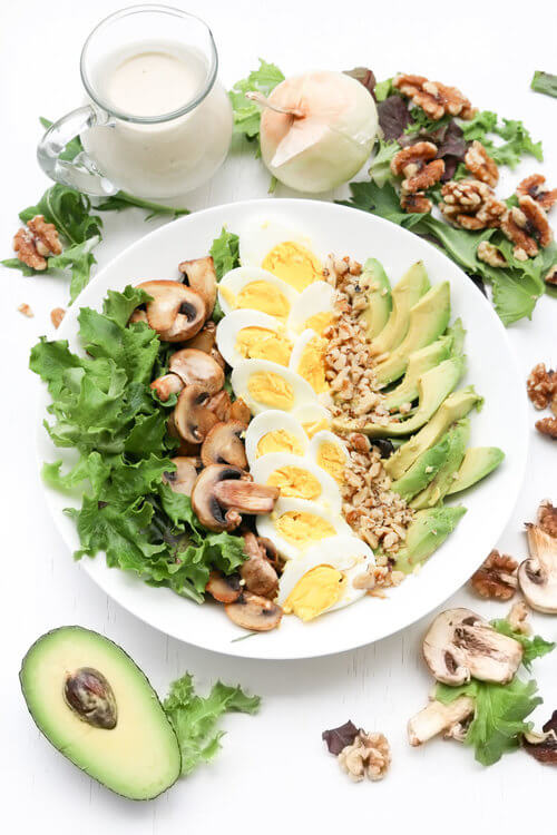 A plate of mushroom egg avocado with homemade sweet onion dijon dressing