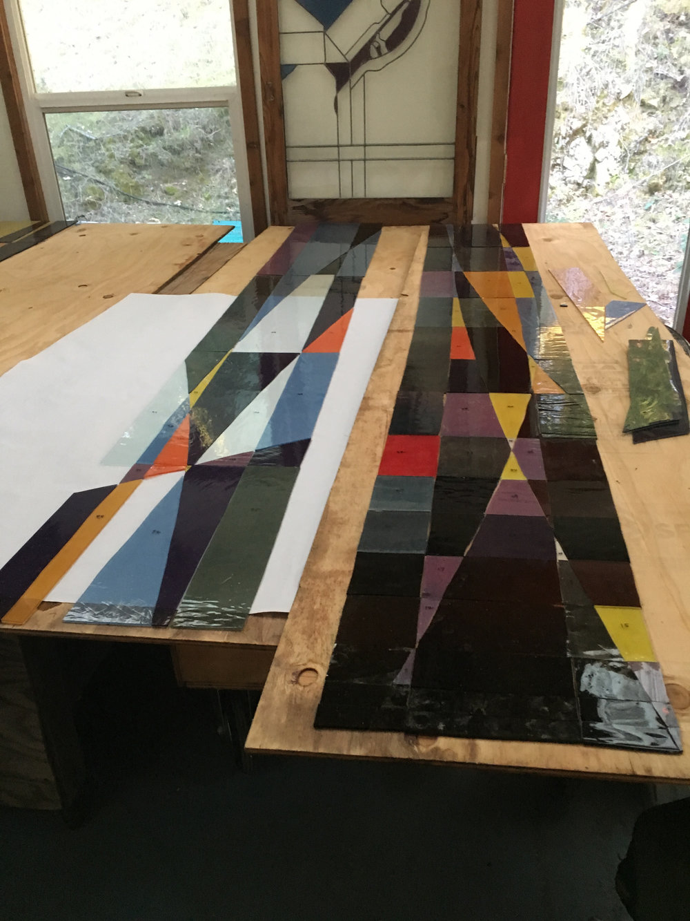 Pieces of window are cut and laid out on a duplicate pattern.