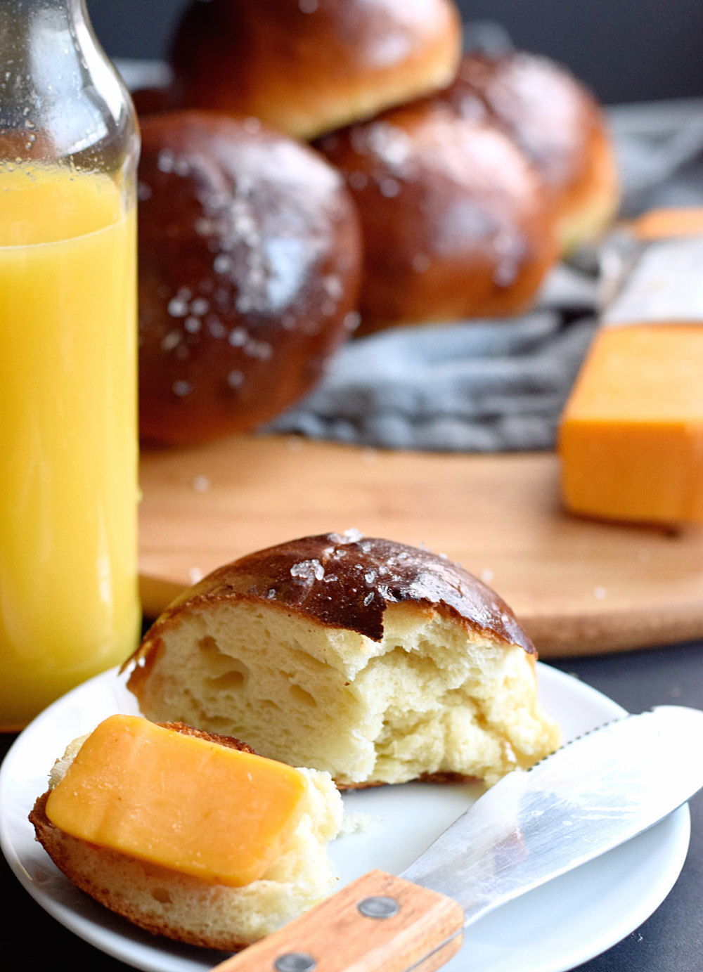 Cheddar Soft Pretzel Buns – soft, fluffy, pretzel rolls filled with cheddar cheese and brushed with melted butter. So, so good! | trufflesandtrends.com