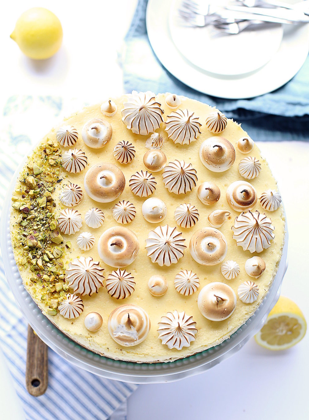 Creamy Lemon Meringue Cheesecake: buttery cookie crust, creamy, tart, spiked lemon filling, and sweet meringue topping. SO good! | TrufflesandTrends.com