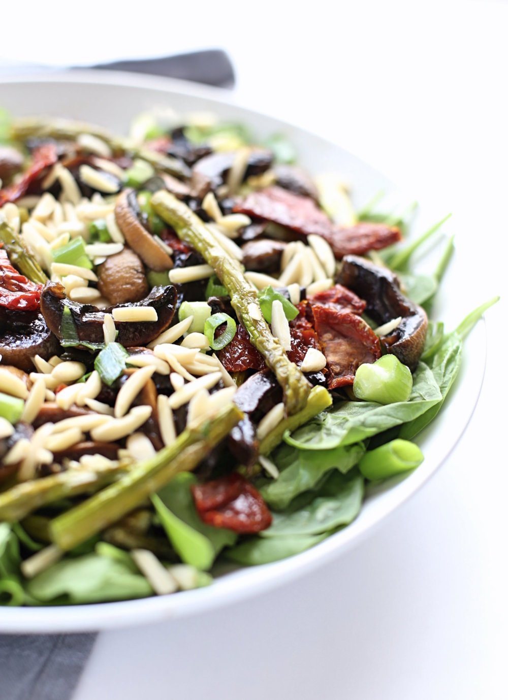 Roasted Asparagus and Mushroom Salad with spinach, sun-dried tomatoes, scallions, basil, and almonds plus an olive oil balsamic honey dressing. | TrufflesandTrends.com