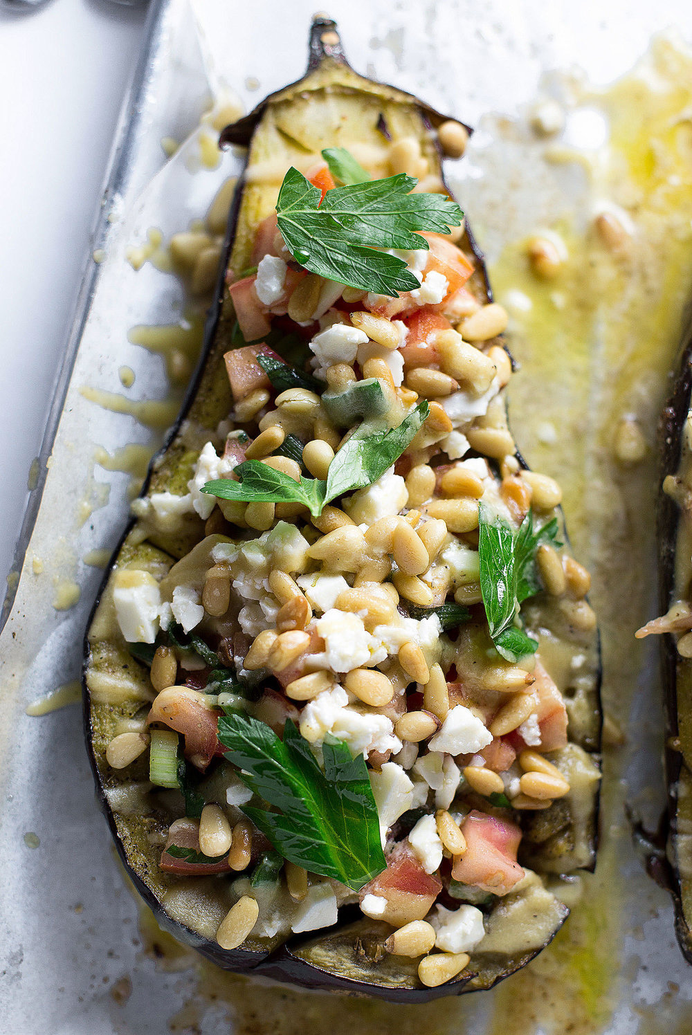Roasted Eggplant with Tomatoes, Scallions, and Tahini: tender roasted eggplant halves with veggies, pine nuts, feta, and an addictive tahini dressing. | TrufflesandTrends.com