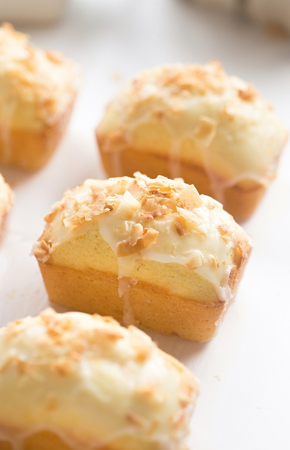 Mini Lemon Coconut Loaf Cakes: easy, soft, fluffy, loaf cakes full of lemon flavor and coconut flakes with a glossy, tangy glaze. | TrufflesandTrends.com