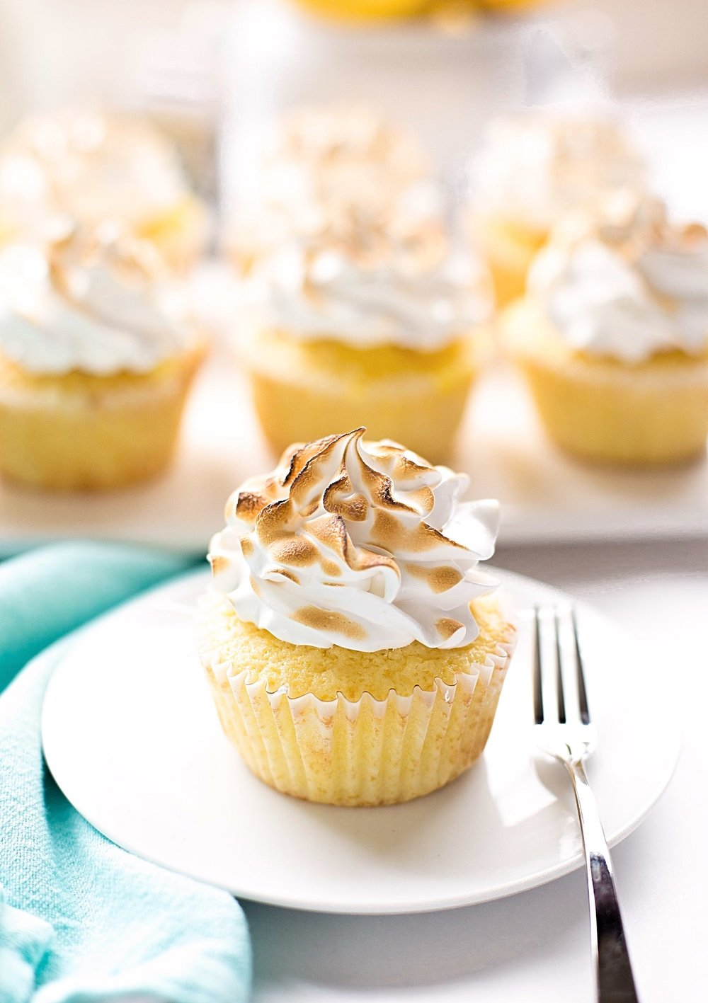 Fluffy Lemon Meringue Cupcakes: soft, fluffy lemon cupcakes filled with a tart lemon curd and topped with a sweet meringue frosting. | TrufflesandTrends.com