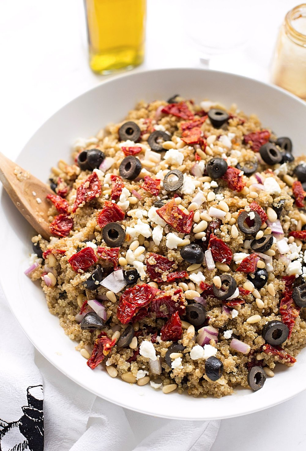 Greek Quinoa Salad: this delicious quinoa salad is made with black olives, red onions, sun-dried tomatoes, feta, pine nuts, and an olive oil, soy, garlic dressing. | TrufflesandTrends.com