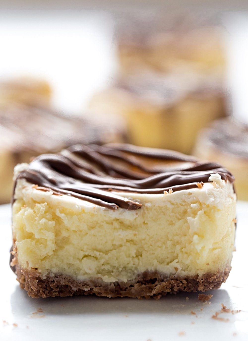 Mini Milk Chocolate Topped Cheesecakes: these personal cheesecakes have a cookie crust, a creamy, sweet and slightly tangy cheesecake filling, and a drizzle of milk chocolate on top. | TrufflesandTrends.com