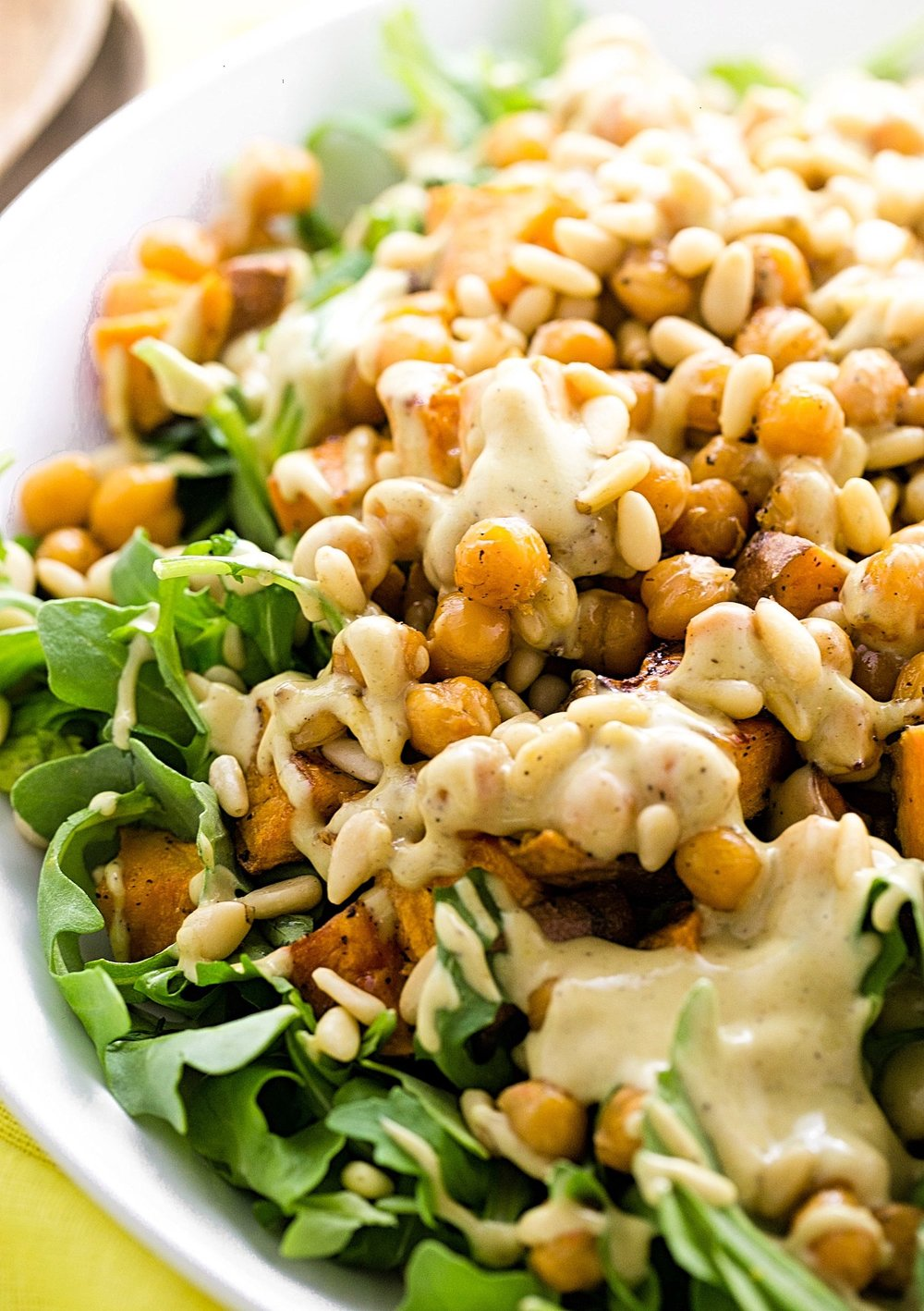 Arugula Sweet Potato Tahini Honey Mustard Salad: arugula and roasted sweet potatoes and chickpeas tossed in a tahini honey mustard dressing. Wholesome and delicious! | TrufflesandTrends.com