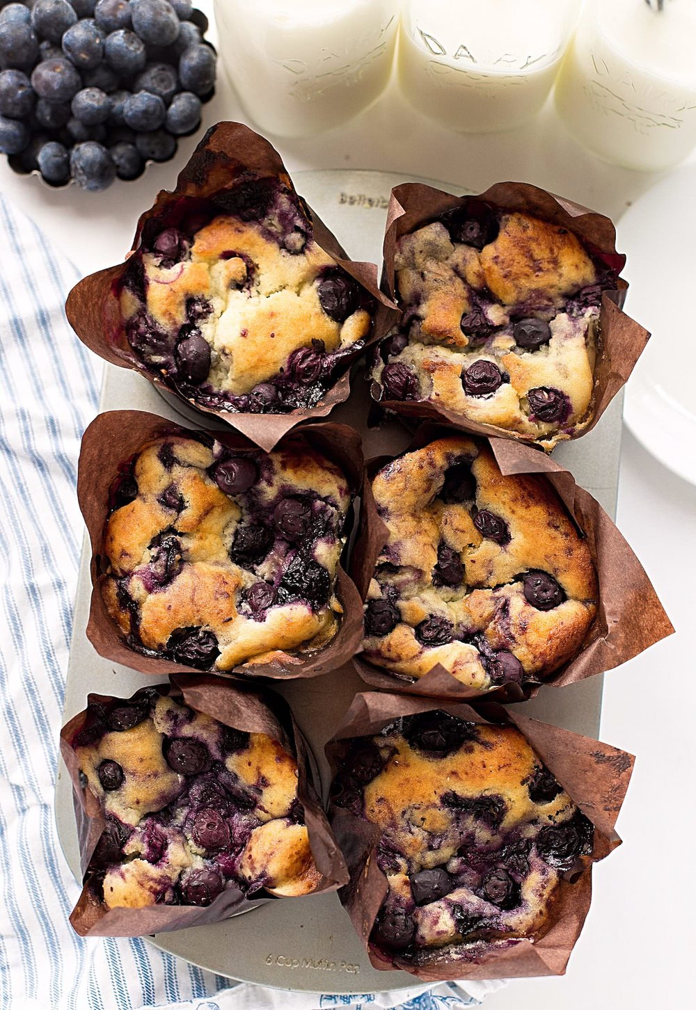Fluffy Blueberry Jam Swirled Muffins: fluffy, tender blueberry muffins with crispy tops and just the right amount of sweetness. Swirled with a homemade, 5-minute blueberry jam! | TrufflesandTrends.com