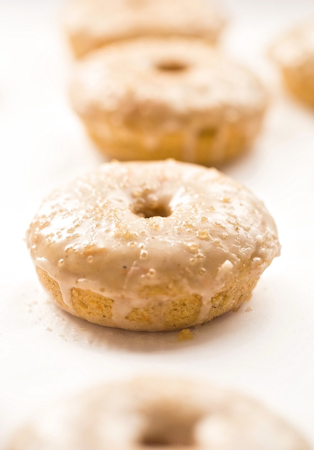 Cinnamon Glazed Baked Carrot Cake Donuts: super soft and moist donuts filled with warm fall spices, freshly grated carrots, and topped with a glossy cinnamon glaze. | TrufflesandTrends.com
