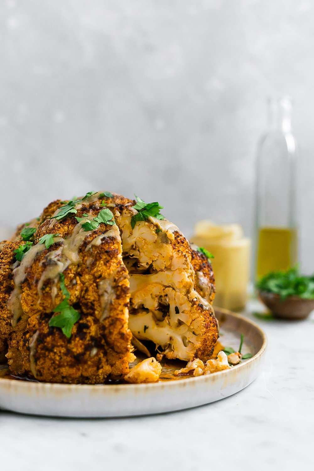 Whole Roasted Cauliflower with Tahini Sauce: tender, flavor-packed roasted cauliflower head with olive oil, generous spices, and a delicious tahini sauce. | TrufflesandTrends.com