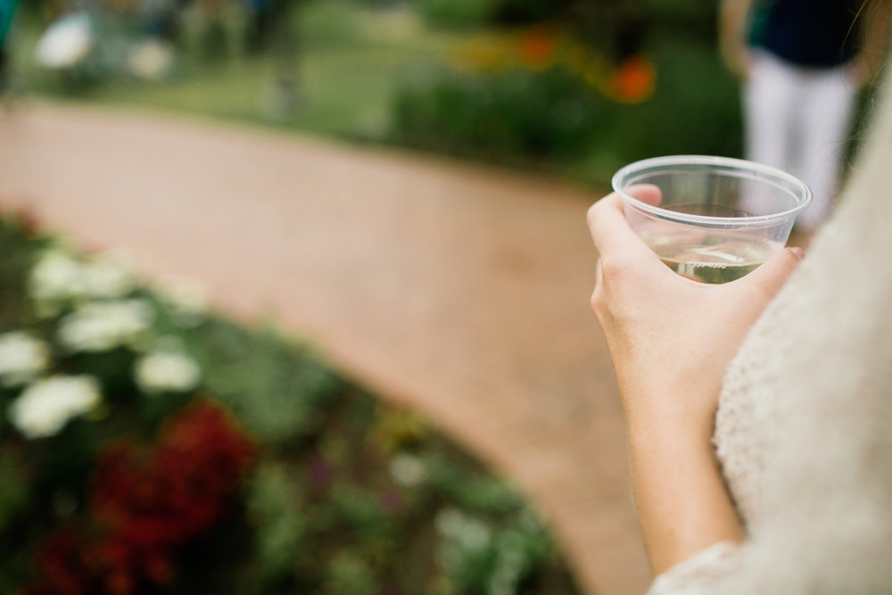 girl holding wine in garden