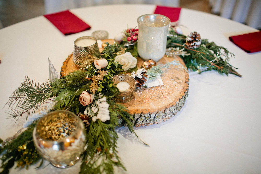 winter wedding centerpieces with evergreen, holly, candles, snow and wood
