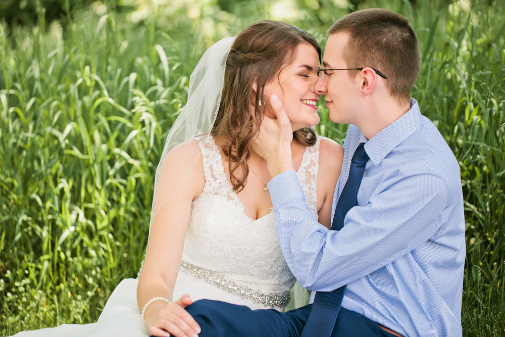 sitting in long grass in blue suit and wedding dress with veil