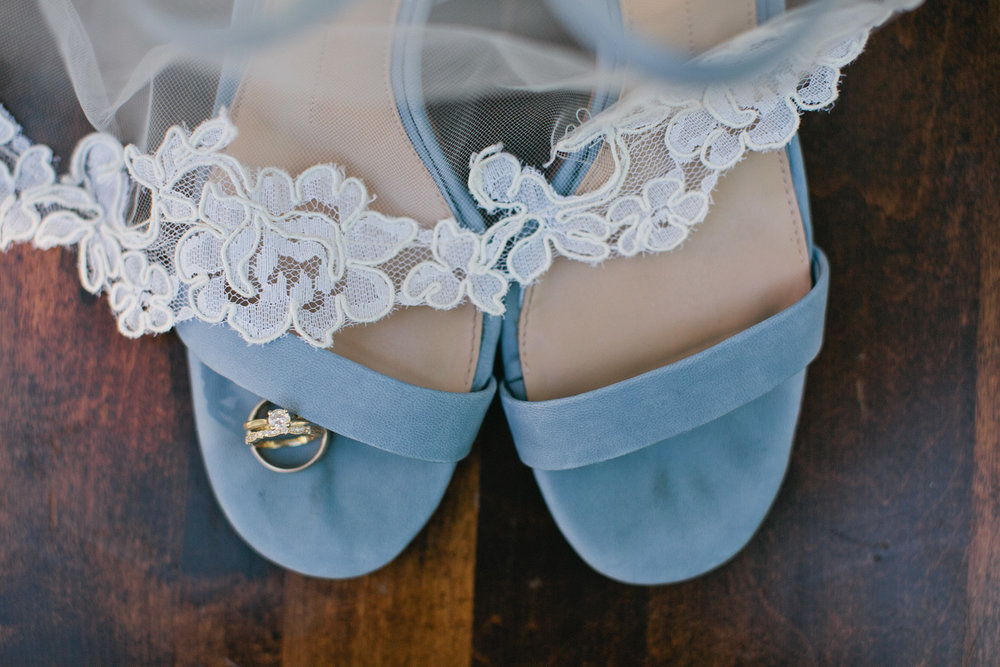 Amelia Renee is a wedding photographer in Omaha. blue shoes lace veil and gold wedding rings