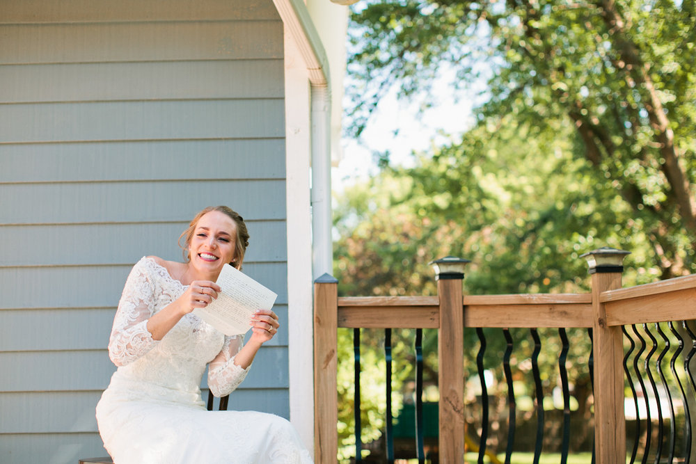 bride reading letter from her groom outside on porch