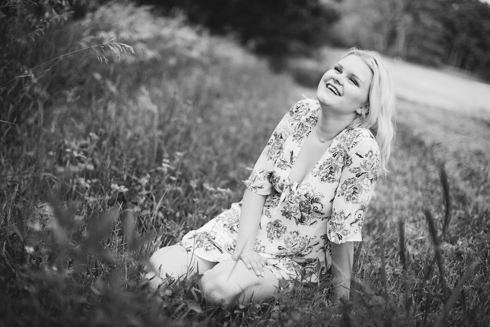 senior in white floral dress laughing in field