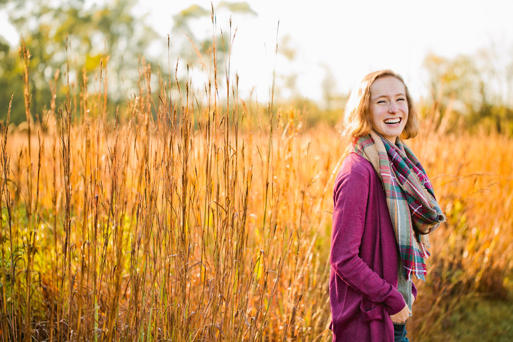 senior girl laughing in wheat field at sunrise in the fall Iowa