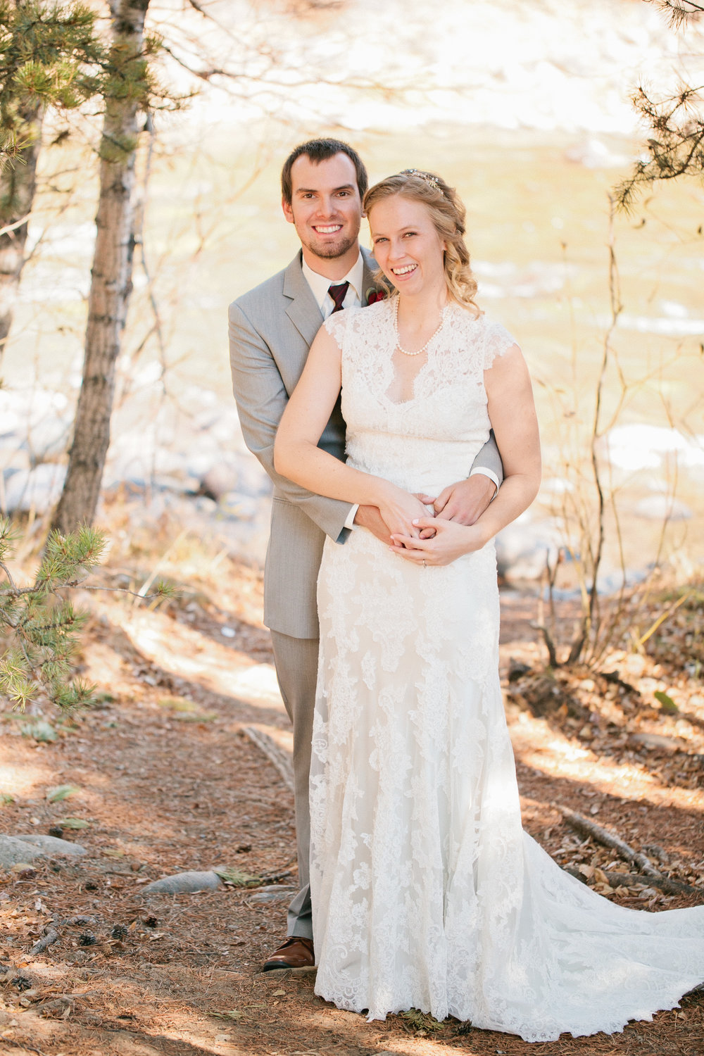 outdoor wedding in Colorado mountains by stream groom wearing a grey suit