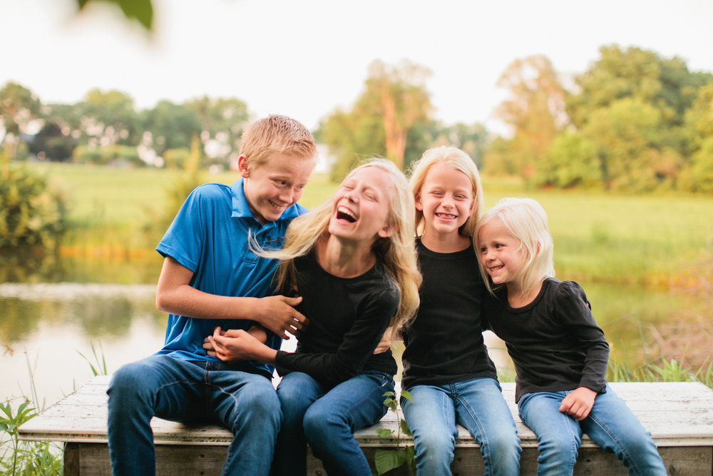 brother and sisters laughing and tickling each other on bench by lake in backyard