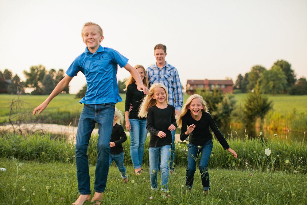 fun lifestyle farm family photos in backyard with barn in Des Moines Iowa