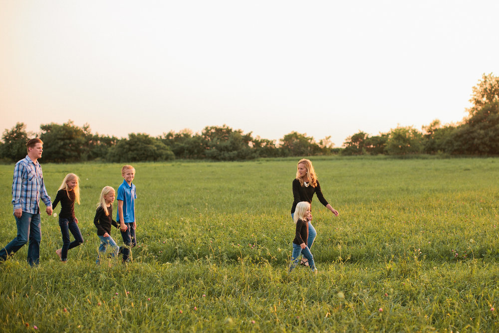 Nebraska farm family photos in clover field at sunset