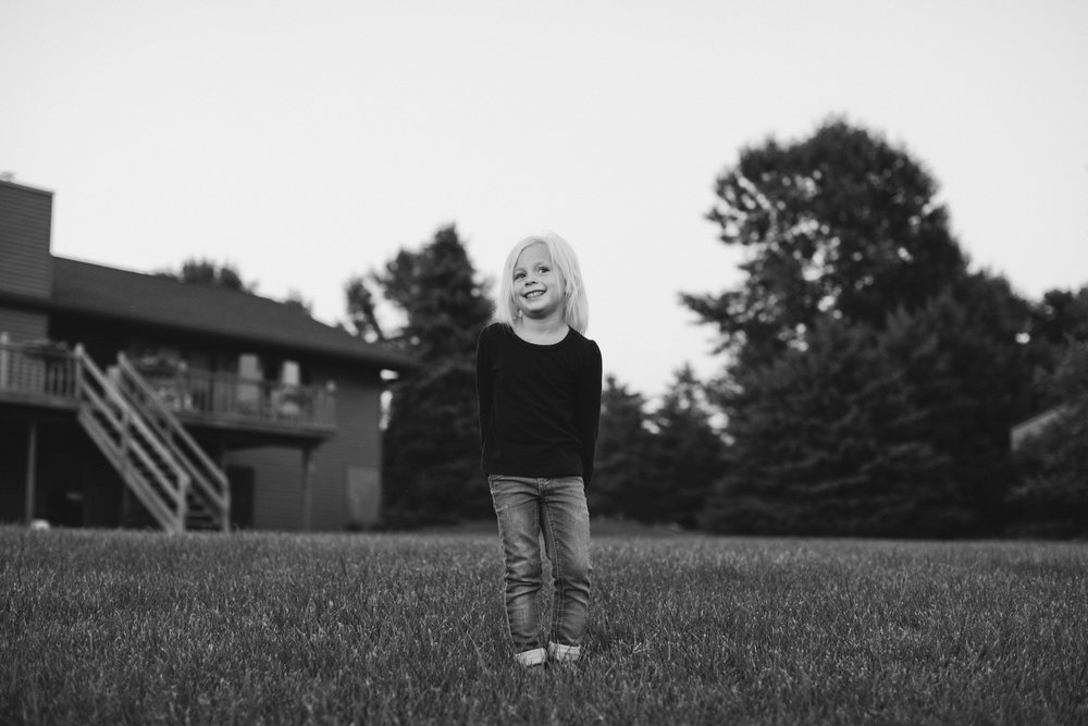 cute little blonde 4-year-old girl smiling wearing jeans and black shirt in backyard