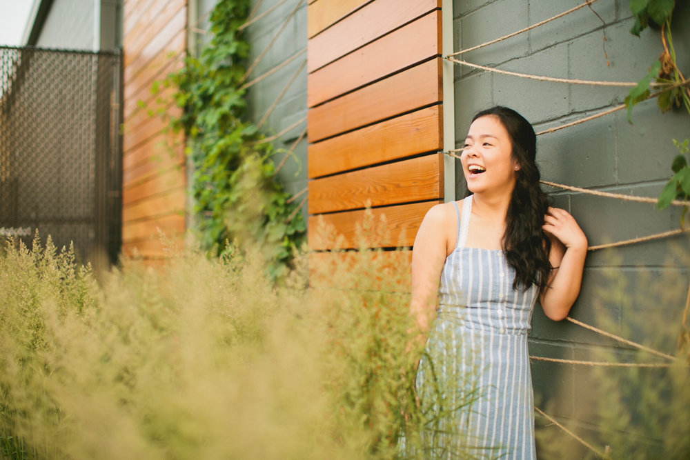 smiling laughing senior photography girl in tall weeds by building