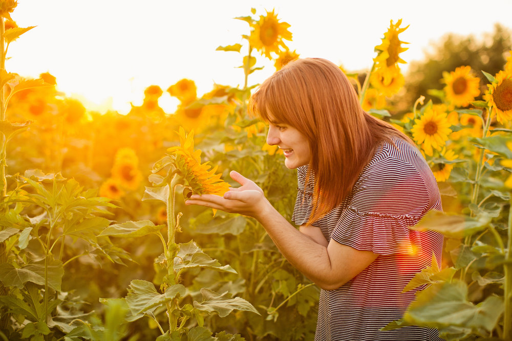 senior photos at sunset in sunflower field girl in hat wearing striped dress smiling